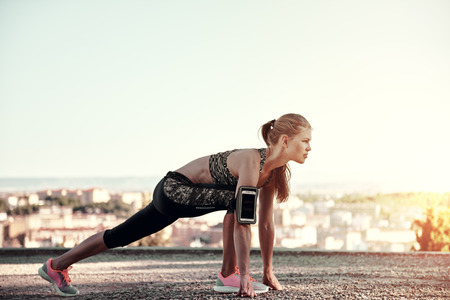 pace: Young sporty female starting to run, standing on the track outdoors. Concept of sport, exercise and healthy lifestyle.