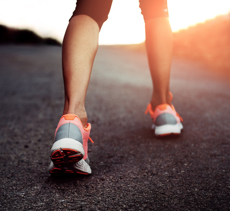 on the move: Close-up of woman runner legs training on asphalt trail in the park at sunset. Concept of sport, travel and lifestyle.