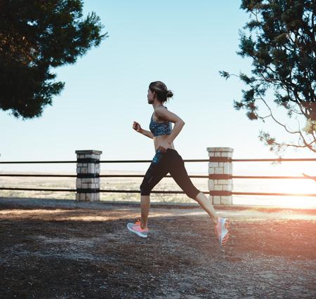 ropa deportiva: mujer joven energético en ropa deportiva para correr al atardecer en el parque. Concepto de la dieta, la salud y la forma física. Foto de archivo