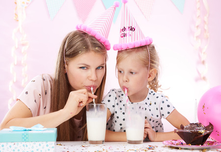fiesta familiar: Young family drinking milk cocktail at birthday party. Concept of holidays and anniversary.