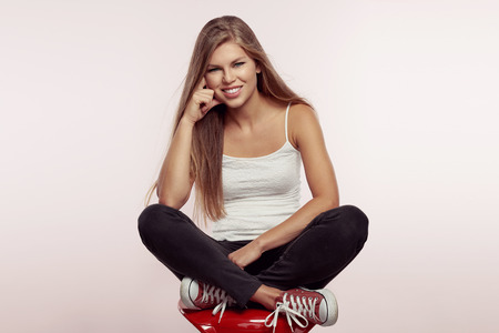 clothing model: Studio portrait of young trendy female model wearing street casual clothing and shoes. Fashion girl sitting on red chair with crossed legs.