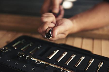 Close-up van mechanische handen die dopsleutel over toolbox veranderen. Concept van reparatie en diy. Stockfoto