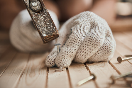 Carpenter with hammer and nails repairing part of furniture on the floor. Concept of construction and woodwork. Stock Photo