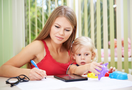 telecommuting: Young busy female telecommuting while her child is playing with toys. Pretty mom with cute daughter checking family bills and documents.