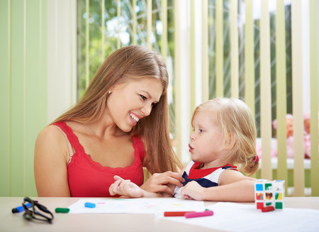Family leisure activity. Young beautiful mother playing with her sweet little daughter at home. Stock Photo