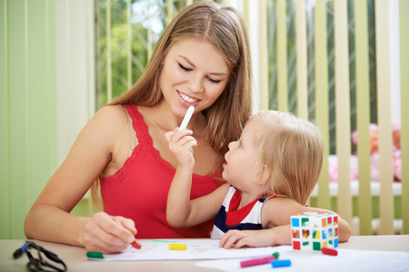 Playful baby girl with her mom painting picture by colorful chalks at the table. Childhood and togetherness concept. Stock Photo