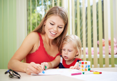 Smiling female and her small daughter drawing with colorful chalks at the table. Concept of child and preschooler development. Stock Photo