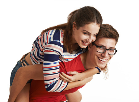feeling happy: Happy young lovers feeling excitement. Studio portrait of handsome man piggybacking his girlfriend over white.