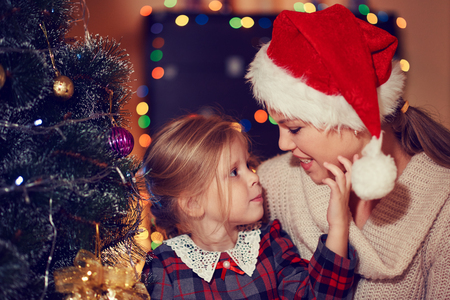 warmth: Adorable girl and her mother hugging at Christmas tree at home. Concept of love, warmth and togetherness.