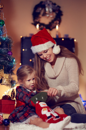 stockings woman: Cute little girl in festive dress sitting on the floor with mum taking sweets from Xmas sock. Family New year tradition and celebration concept.