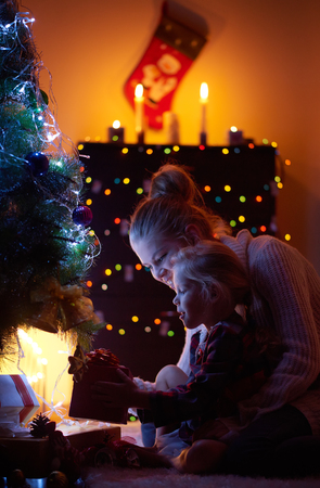 christmas winter: Portrait of family getting Christmas presents sitting at new year tree in the house. Happy young woman with small daughter celebrating winter holidays in the evening. Stock Photo