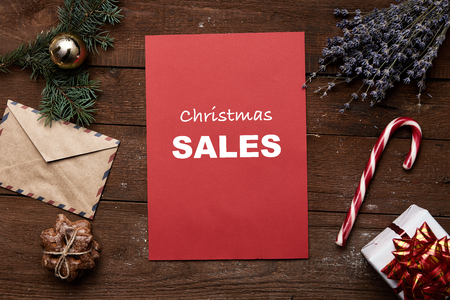 red sheet: Christmas sale and price reduction. Red sheet, gift box, candy, lavender, pine, ball, envelope and gingerbread on wooden table. Stock Photo