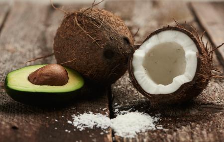 Avocado and broken coconut on dark wood background. Exotic drink ingredients.