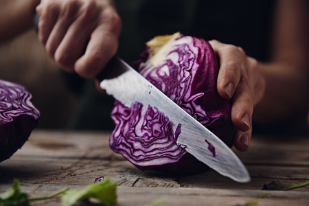 Housewife chopping red cabbage on wooden board in the kitchen.