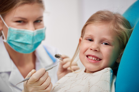 treating: Happy smiling child sitting on dental chair ready to cure teeth. Portrait of woman dentist in mask with tools treating patient. Stock Photo