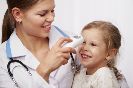 medical test: Woman pediatrician measuring temperature of little girl. Concept of medical examination or test.