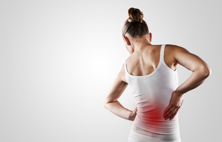 lumbar: Portrait of young woman touching her painful back over grey background with copy space. Concept of backbone disease therapy.