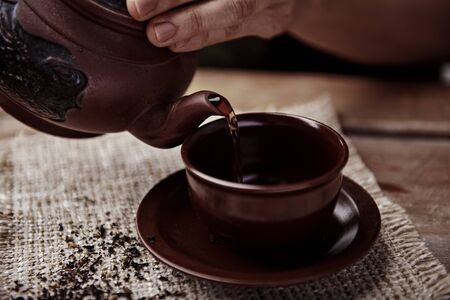 Closeup of woman hands pouring hot herbal tea from teapot on wooden table.