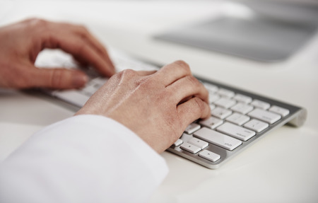 medical practitioner: Woman practitioner typing medical report on keyboard at the desk. Stock Photo