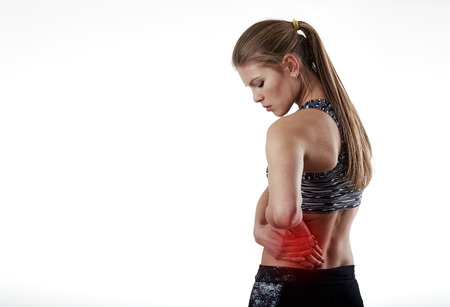 Sportswoman touching sore left side. Concept of hip injury and pain. Stock Photo