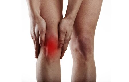 Young woman massaging painful knee. Concept of concept of leg injury or spasm. photo