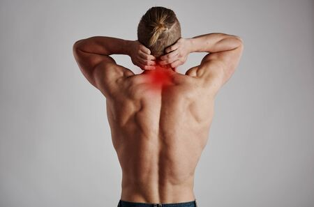 Neck pain. Athletic man massaging his inflamed spine. Stock Photo