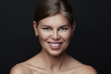Beauty portrait of attractive Caucasian female over black background. Concept of skincare and face perfection. photo