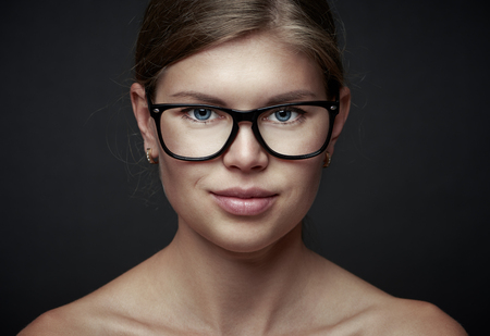 Young pretty female wearing eyeglasses over dark background. Concept of vision correction and ophthalmology. photo