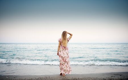 Beautiful portrait of stylish female in floral dress looking at blue water and ocean horizon at the dawn.