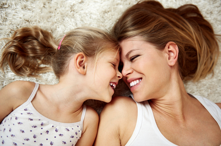 Pretty smiling girl with her mother lying on the floor and looking at each other in happiness. Stock Photo