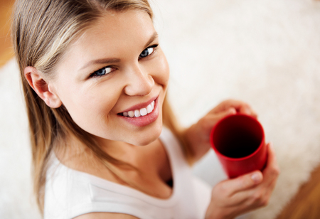 Close up of young attractive female with tea mug relaxing at home.