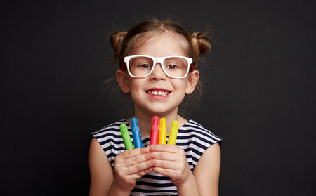Cute smiling girl wearing eyeglasses holding colorful pencils. Little preschool kid posing over black background.