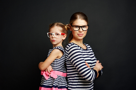 Beauty portrait of young female and cute girl wearing eyeglasses. Concept of optometry and vision.