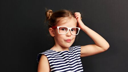 Studio portrait of adorable girl having doubts. Pretty child in eyewear thinking, posing on dark background. Stock fotó