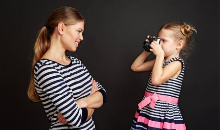 Cute girl taking picture of her mother in studio over black background.