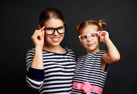 Beautiful girl with her mom wearing spectacles over black background. Concept of healthy vision and eyesight correction.