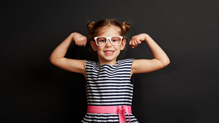 Pretty smiling child showing biceps muscles over dark background. Concept of power and success. Stock fotó