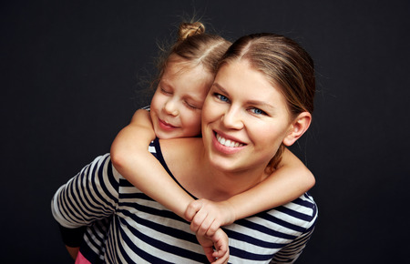 Portrait of beautiful young woman givving her daughter piggyback over studio background. Parenthood concept.