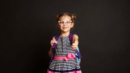 Pretty smiling girl in spectacles wearing backpack, ready for the first school day. Happy child showing thumb up over studio background. Stock fotó