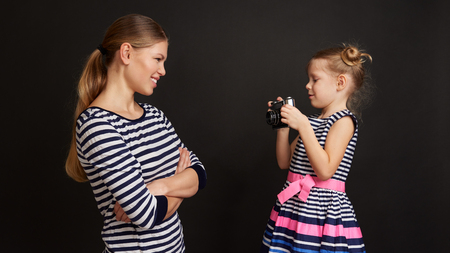 Pretty smiling female posing at camera. Adorable girl with vintage camera taking photo of her mum.