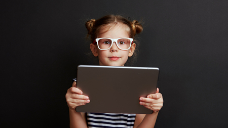 Portrait of smart girl holding digital tablet over black background. Concept of childhood and technology.