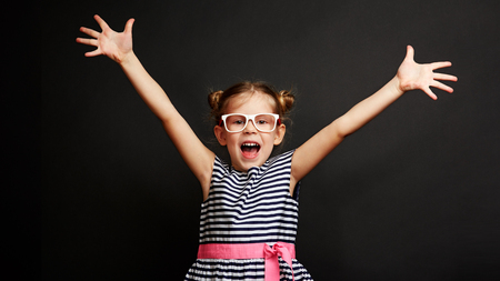 Happy little girl winning success. Cute kid standing with hands up and open mouth over black studio background.