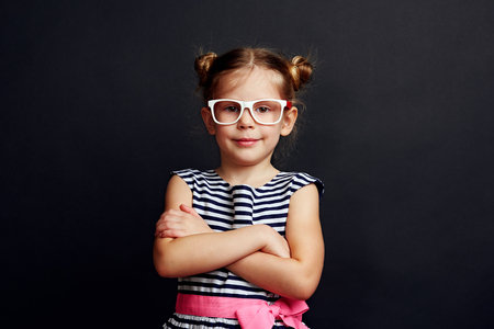 Fashion portrait of adorable girl in specs with stylish hairdo over studio background.