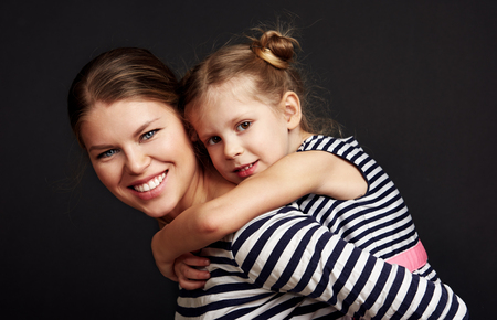 Happy smiling mother piggybacking her cute daughter. Little girl embracing mother over studio background.