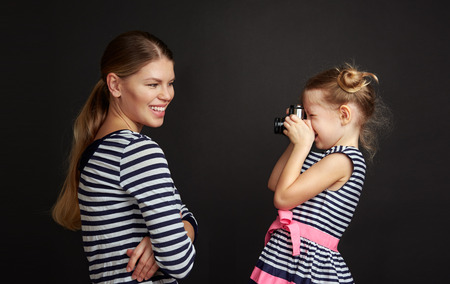Little girl photographing her cheerful mom with old vintage camera over studio background.