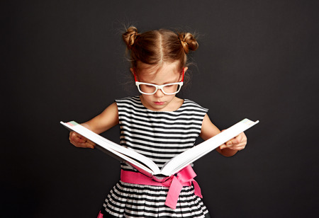 Little pupil in glasses holding big book and reading. Education and knowledge concept. Stock fotó