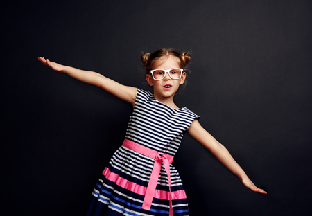 Portrait of charming girl imagining airplane fly. Cute kid in stylish dress and glasses over studio background.