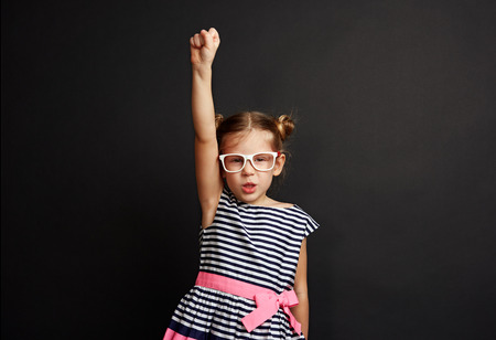 Cute girl wearing spectacles standing with hand up like superhero. Studio portrait of little child winning success. Stock fotó
