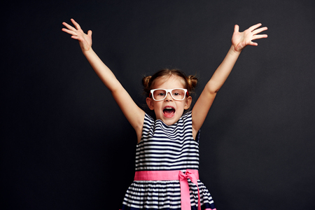 Emotional little girl standing with hands up and crying. Happiness, childhood and success concept. Stock fotó
