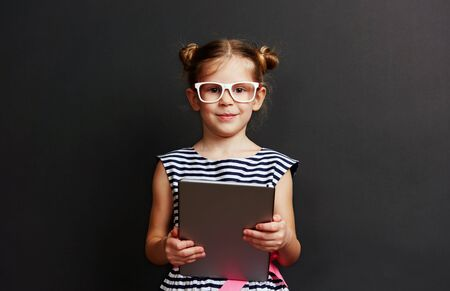 Adorable little girl in glasses holding digital computer on black studio background.